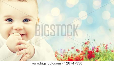 children, people, infancy and age concept - beautiful happy baby over blue lights and poppy field background