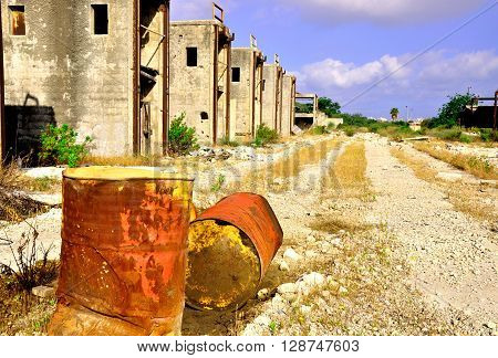 Rusty barrels and derelict  buildings in abandoned industrial zone.