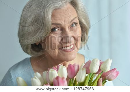 Senior woman portrait with blooming tulips flowers ** Note: Visible grain at 100%, best at smaller sizes