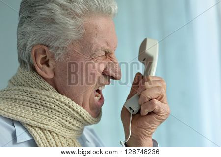 Portrait of an angry senior man with phone