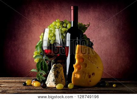Cheese and wine with grape on vinous background