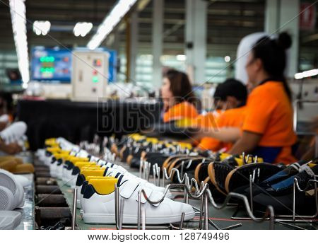 worker making sport shoe in footwear production line