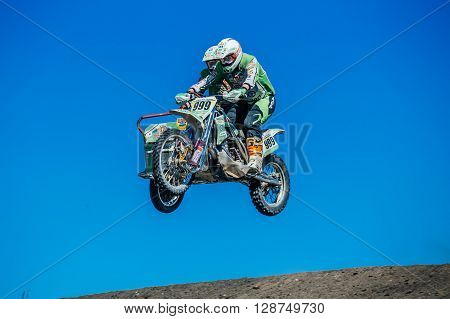 Miasskoe Russia - May 02 2016: motorcyclist with a sidecar jump from a mountain on background of blue sky during Cup of Urals motocross