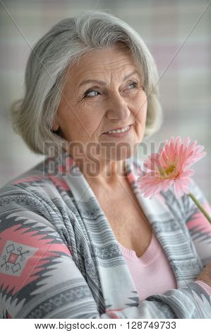 Portrait of a happy senior woman with flower