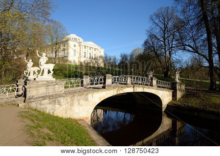 Bridge over the river Slavyanka and Palace in Pavlovsk at sunny spring day on the outskirts of St. Petersburg Russia.