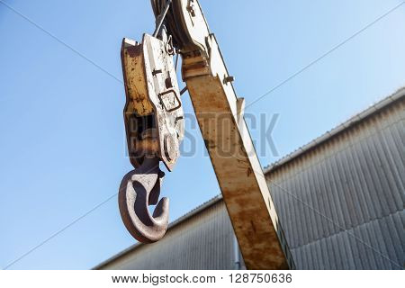 a yellow crane hook on a building