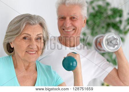 Happy sporty senior couple exercising with dumbbells