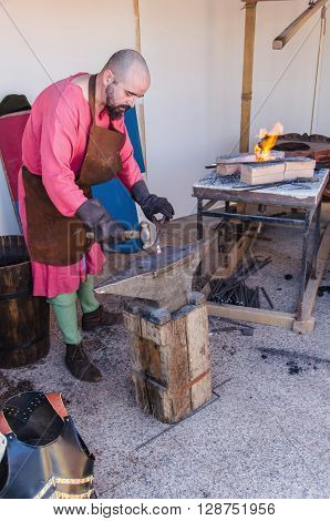 Blacksmith Working In A Medieval Forge