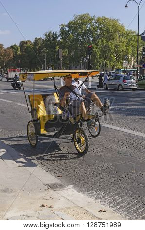PARIS FRANCE - SEPTEMBER 16 2014: Carriage taxi being driven by man along the paris street in summer