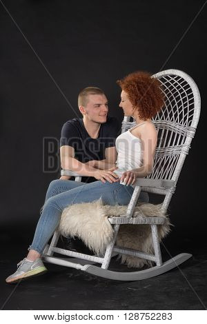 Portrait Of Young Couple Sitting On A Wicker Rocking Chair, Studio Shot, Dark Background