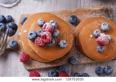 Home-made breakfast or brunch: american style pancakes served with berries and sugar powder on an old cutting board with a cup of black tea