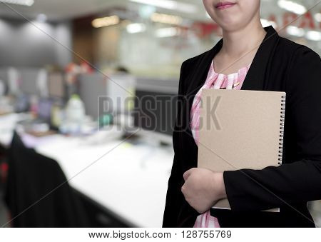 One smart business woman wear black suit and hold brown notebook in left hand stand on office background (Business concept)