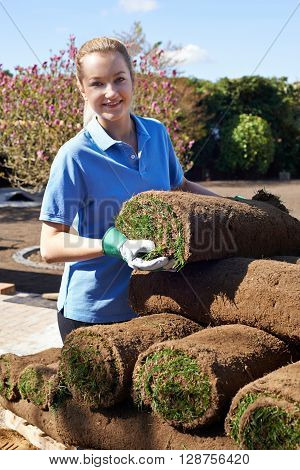 Female Landscape Gardener Laying Turf For New Lawn