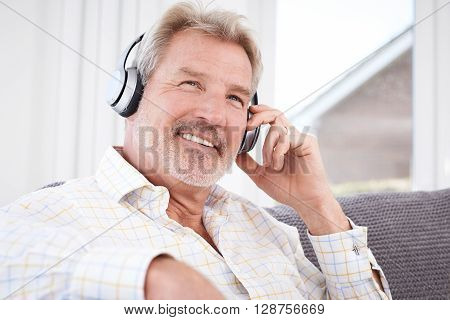 Mature Man Listening To Music On Wireless Headphones