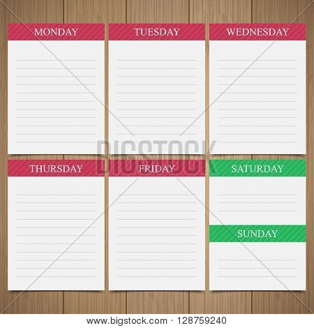 Weekly planner in paper notes on a wooden background