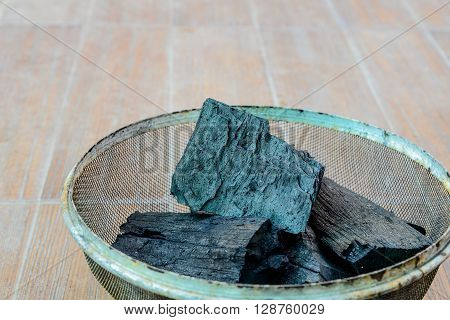 Charcoal in steel grating placed on cement floor.