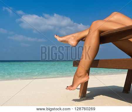 Young woman sunbathing on lounger. Legs on sea background