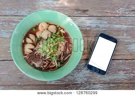 Thai noodle in green Bowl White display Smart phone beside bowl noodles.All placed on wooden table.