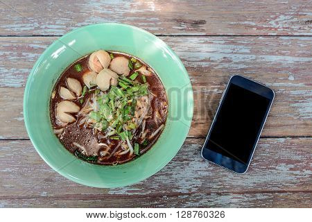 Thai noodle in green Bowl Black display Smart phone beside bowl noodles.All placed on wooden table.