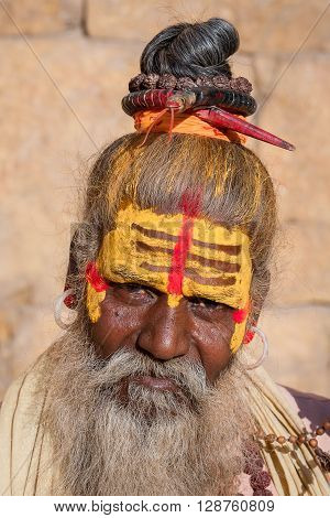 Hindu sadhu holy man sits on the ghat seeks alms on the street in Jaisalmer Rajasthan India . Close up