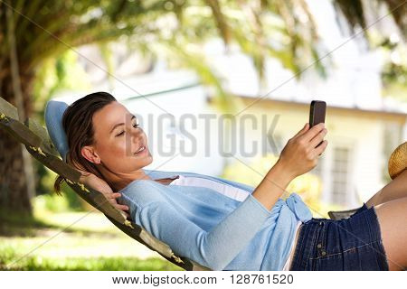 Young Woman Relaxing On A Hammock With A Mobile Phone