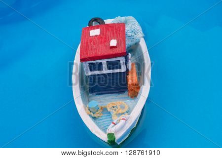 Little model fishing boat in water on a blue background