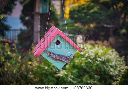 The birdhouse with a pink roof close-up