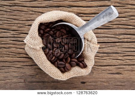 hemp sack of brown roasted coffee with scoop on wood background from top view