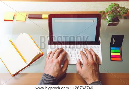 Man sitting at a table, working behind the laptop. Mock up. View from above. Telework concept