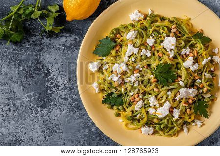 Homemade Zucchini Zoodles Pasta with Pine nuts and Feta top view.
