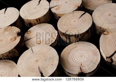 Many pine saw cuts with cracked of different thicknesses are arranged diagonally on a black background