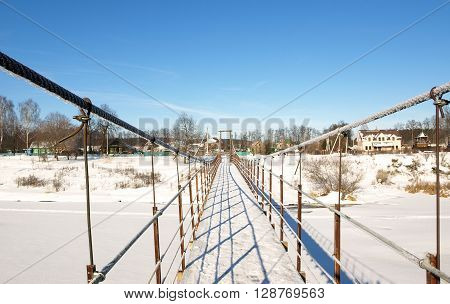 Frozen suspension bridge across the river in winter