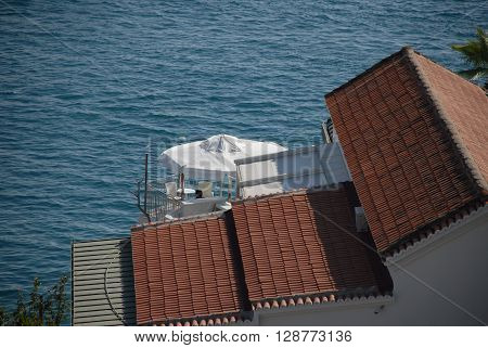 ANTALYA/TURKEY-19 OCTOBER 2014-Building's roof and white umbrella at the coast near the Konyaalti Beach Antalya Province Turkey