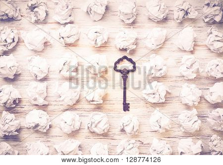 Vintage key among many balls of crumpled paper