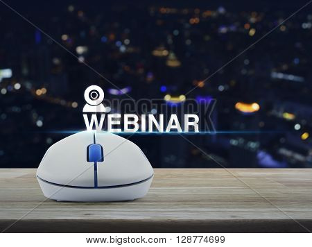 Wireless computer mouse with webinar icon on wooden table in front of blurred light city tower Seminar online concept