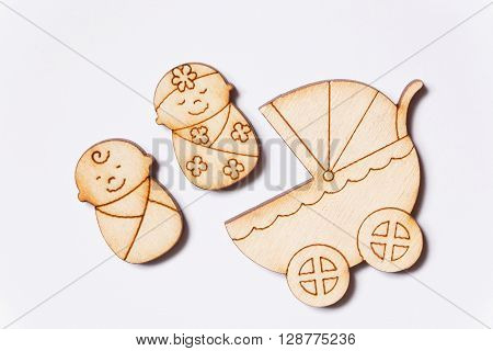 Newborn boy and girl near baby carriage. Wooden pieces cut out in the forms of children for childcare concept.