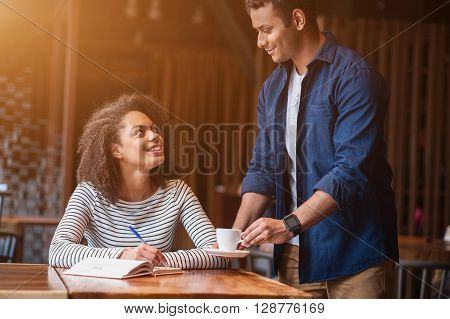 Pretty young woman is sitting in cafe. The man is holding a cup of coffee and putting it on her desk. They are flirting and smiling