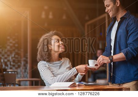 Take young cup of coffee. Attractive male waiter is serving a woman is cafe. He is standing and giving her a cup. They are flirting and smiling