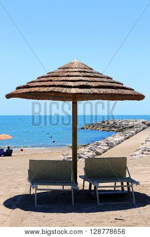 Beach With Parasols Made With Bamboo And Straw In The Resort