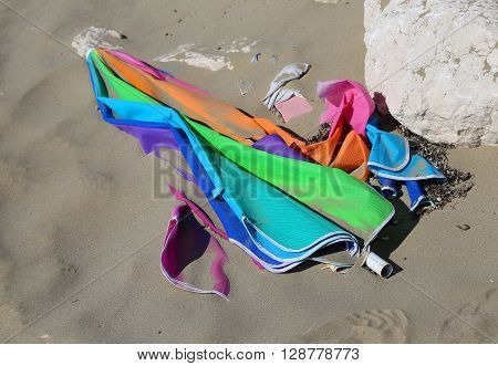 Broken Colored Abandoned Parasol At The Sandy Beach