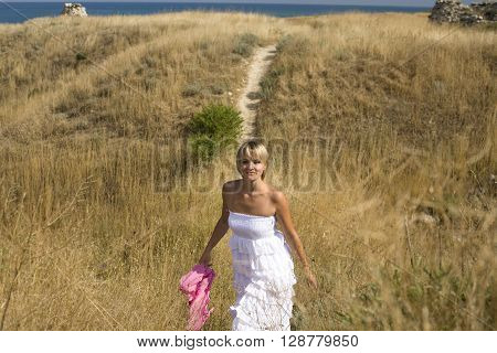 portrait of beautiful blond woman in white dress standing on wind with scarf near sea among yellow grass, lifestyle vacation concept