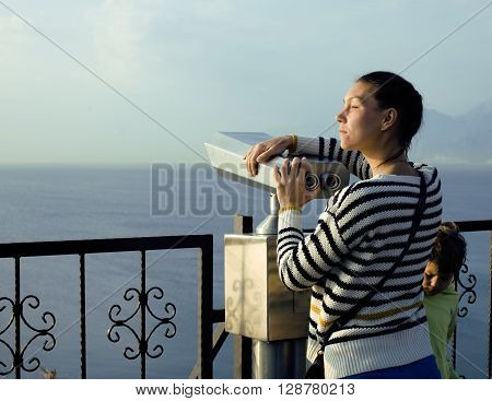 young real woman looking through telescope at sea viewpoint in Ataturk park, sunny morning, lifestyle people concept