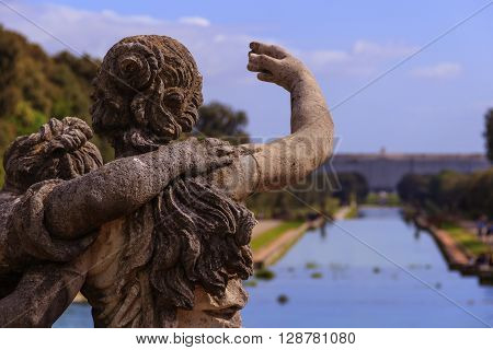The Royal Palace of Caserta: the garden. Italy (Campania).Detail of a sculpture.View of the northern facade from the middle of the Garden.