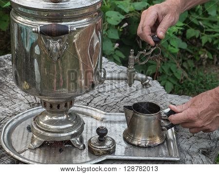 The tea party outdoors. Man makes tea with water from boiling old samovar.