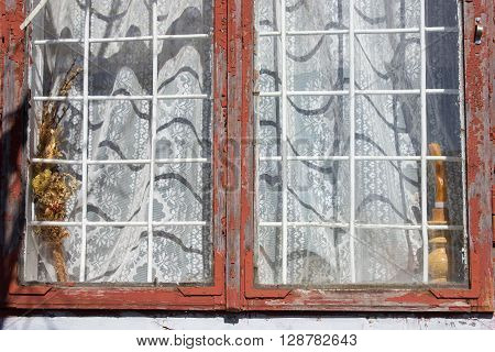 Window bars with old metal and white curtains on the window