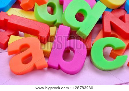 Colorful letters word ABC on pink wooden table