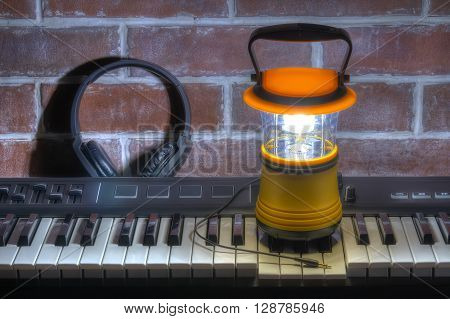 Luminous hand lantern standing on MIDI-keyboard with headphones on the background of the brick wall HDR processing