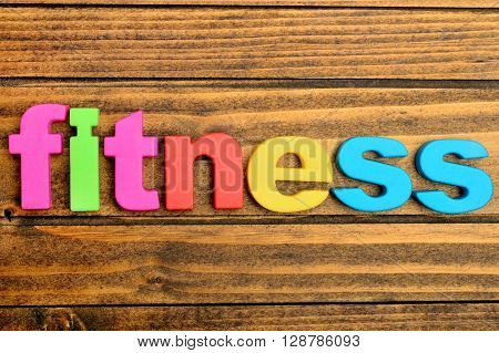 Colorful letters word Fitness on wooden table