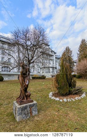 Bronze Woman Statue In The Park . Cold Day, Nobody In The Park, Bronze Statue, Surrounded By Firs, S