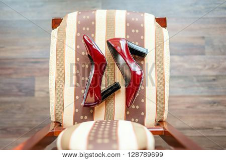 Baroque chair and red women's shoes  in an empty room